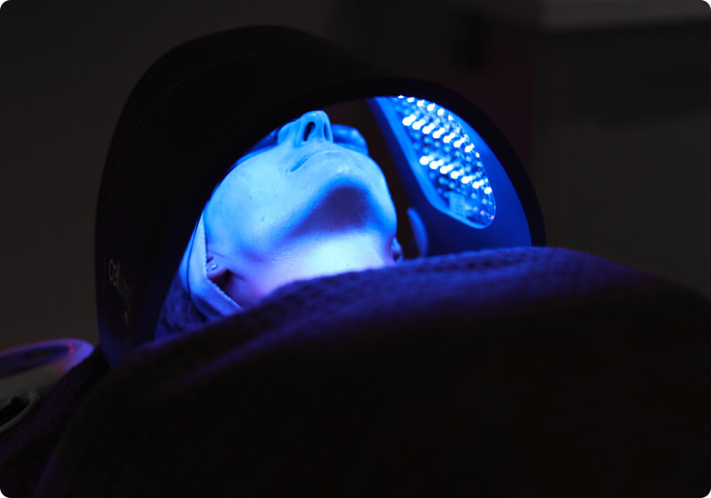 Lady using a LED light therapy treatment on her face