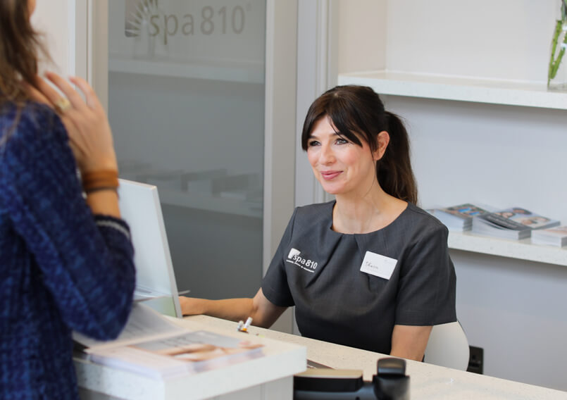 Therapist greeting a customer at the spa810 counter